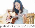Beautiful woman playing guitar at home 66236059