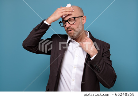 italian businessman in suit and glasses wiping sweat 66248859