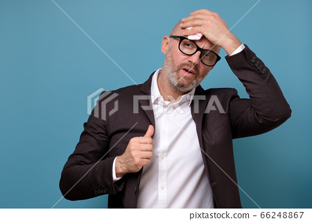 italian businessman in suit and glasses wiping sweat 66248867