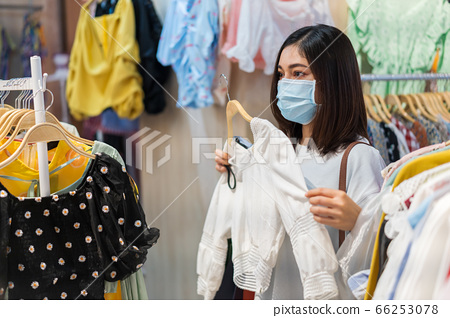 woman choosing clothes at shopping mall and her 66253078