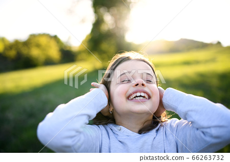 Portrait of small girl standing outdoors in spring nature, having fun. 66263732