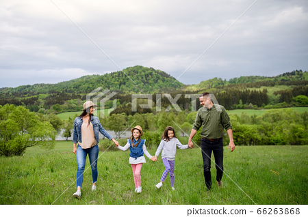 Happy family with two small daughters walking outdoors in spring nature. 66263868