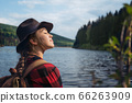 Young woman standing outdoors by lake on a walk in summer nature, relaxing. 66263909