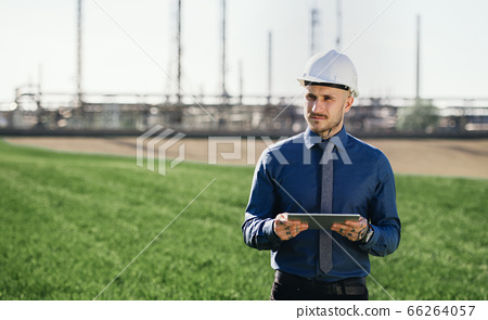 Young engineer with hard hat and tablet standing outdoors by oil refinery. 66264057