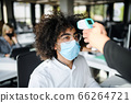 Young man with face mask back at work in office after lockdown, measuring temperature. 66264721