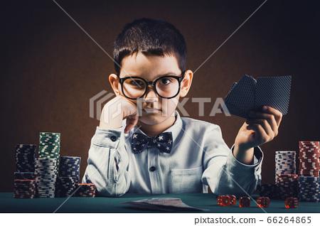 Little kid boy playing poker in a casino. 66264865