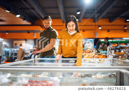 Family couple at the refrigerator in grocery store 66276828