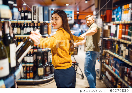 Funny couple in grocery store, alcohol department 66276830