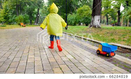 Cute little boy in yellow raincoat running with toy truck under rain at park 66284819