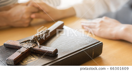 Christian woman praying with hands together on holy bible and wooden cross. 66301609