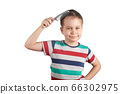 Little boy in a T-shirt combing his hair, isolated on white background 66302975