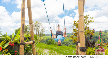 Happy female traveller swinging on wooden swing, enjoying summer vacation among pristine green rice terraces. 66306527