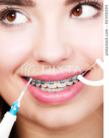 Woman with braces cleaning teeth with toothbrush 66306894