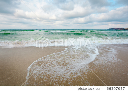 sea tide on a cloudy evening. waves crashing sandy 66307057