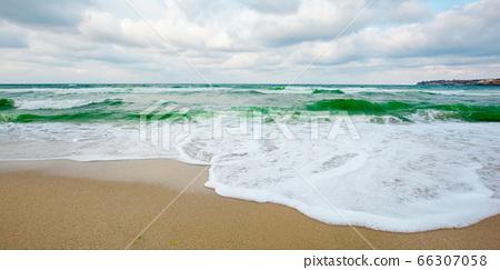 sea tide on a cloudy evening. waves crashing sandy 66307058