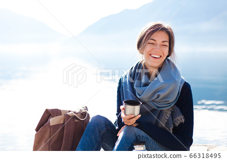 Young woman reading book at sea beach. Cozy winter picnic by morning mountains. Happy student 66318495
