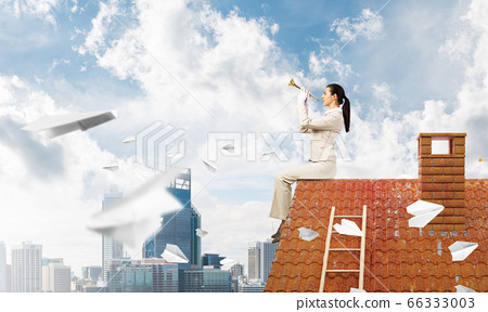Young woman playing trumpet and sitting on roof 66333003