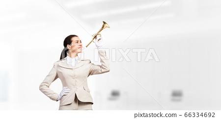 Beautiful woman playing trumpet brass 66334692