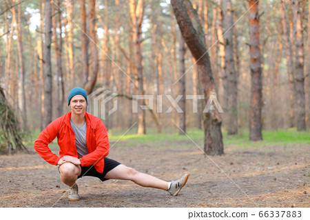 Young boy doing stretch marks in park, morning. 66337883