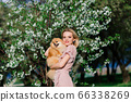 Attractive young woman holding dog spitz outside 66338269