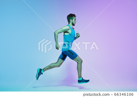 Full length portrait of active young caucasian running, jogging man on gradient studio background in neon light 66346106