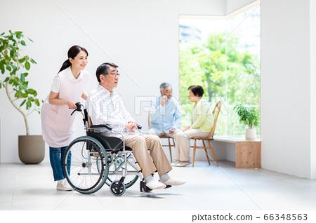 휠체어 수석 남자와 간호하는 젊은 여성 66348563
