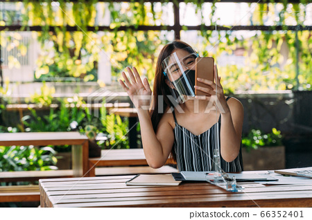 Happy Asian woman smiling wearing face shield holding a mobile phone on terrace. Video calling technology during Covid-19 - Corona Virus 66352401