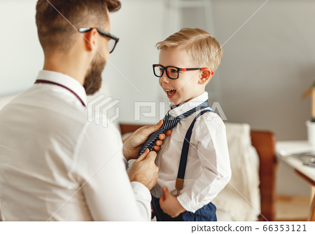 Father dressing son at home. 66353121