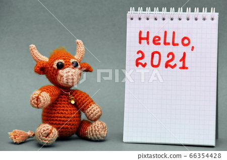 The symbol of the New year 2021. The toy bull on a  a gray background. 66354428