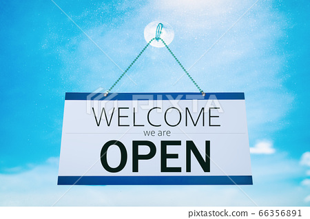 COVID-19 WELCOME we are Open for business hanging on store front window sign for stores reopening after coronavirus. Cafe, businesses, restaurants, reopen again. Sunny summer blue sky window 66356891