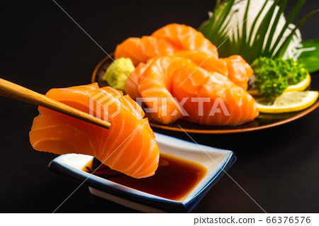 Sashimi, Salmon, Japanese food chopsticks and wasabi on the wood table 66376576