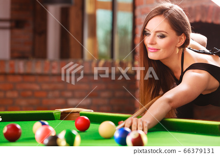 Young woman having fun with billiard. 66379131