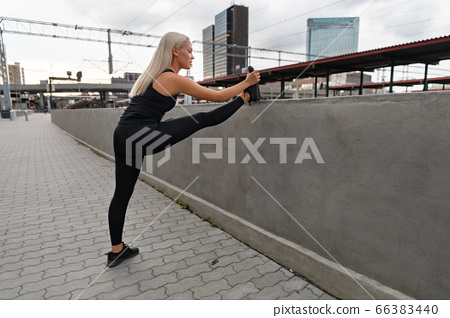 A young female runner stretching her muscles before jogging 66383440
