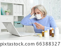 Ill beautiful senior woman with facial mask holding thermometer 66388327