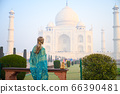 Portrait of young woman in Turquoise blue saree indian traditional dress against Taj Mahal 66390481