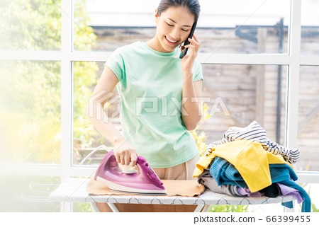 熨烫家务的人材料时的年轻家庭主妇女人手机 66399455