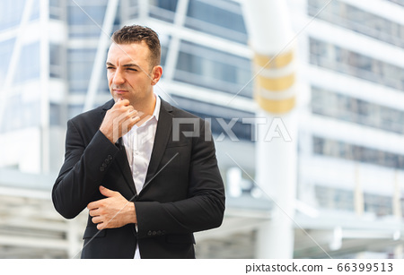 Handsome young business men in black suits standing in middle of city. 66399513