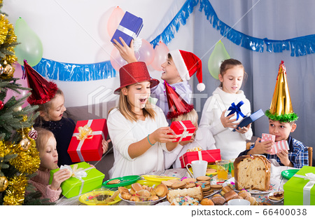 children presenting gifts during Christmas dinner 66400038