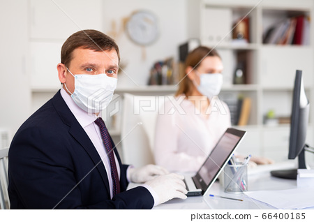 Portrait of businessman in protective medical mask at office 66400185