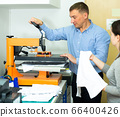 Man and woman printing t-shirt in a workshop 66400426