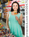 sexy young female posing in the store with lolly 66400475