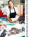 Saleswoman demonstrating fresh raw salmon 66400618