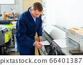 Service man uses plotter in printing shop 66401387