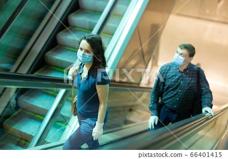 Metro passengers in protective masks climb the escalator 66401415