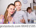 Little girl and mother with mature medical worker 66401585