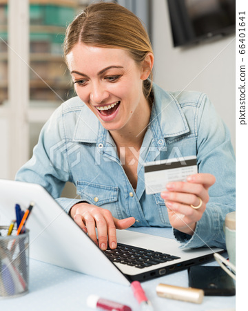 Girl buying online with laptop and credit card at home 66401641