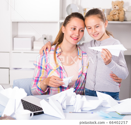 Woman and girl making airplanes of pape 66402257