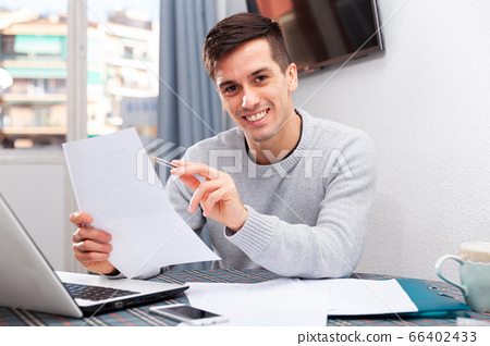 Young happy man sitting at home table working with papers, analyzing domestic budget 66402433