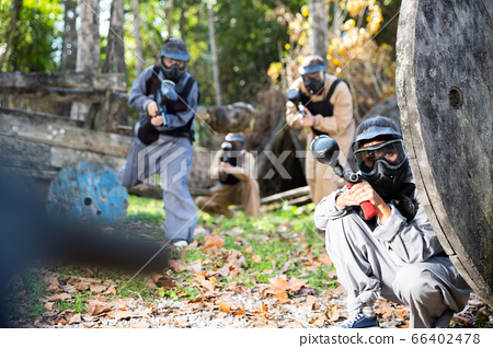 Men and women playing paintball 66402478