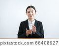 Young woman in a suit talking from the camera 66408927